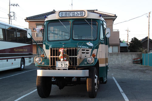 乗客を降ろして駐車場に止まるボンネットバス