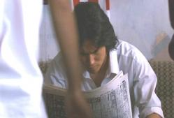 スポーツ新聞を見ている安仁屋