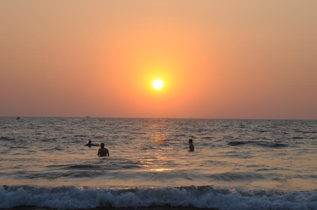 アラビア海の夕日に泳ぐ人々