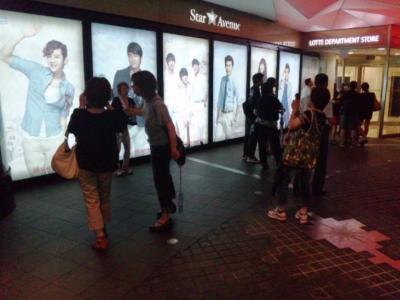 ロッテ免税店入口の韓流スターの看板と撮影する日本人女性