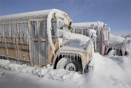 米ネブラスカ州のボウリング場の裏にある駐車場で、氷と雪に覆われたバス。暖かくなっても、きちんと動くか心配