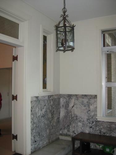 玄関内部。腰壁には大理石が ...