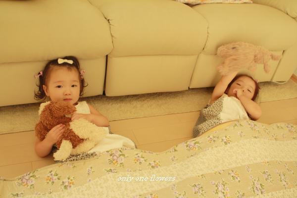 フロアマットを掛け布団にする姉妹。
