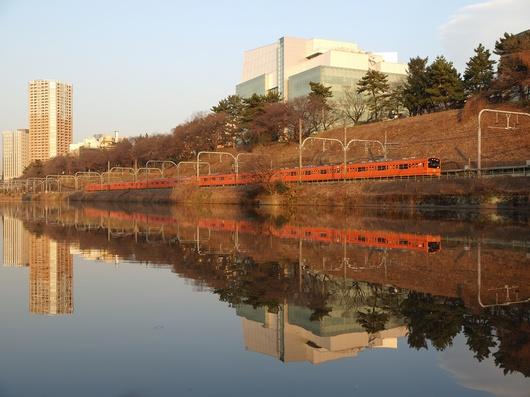 夕日を浴びて外堀をゆくオレンジの電車