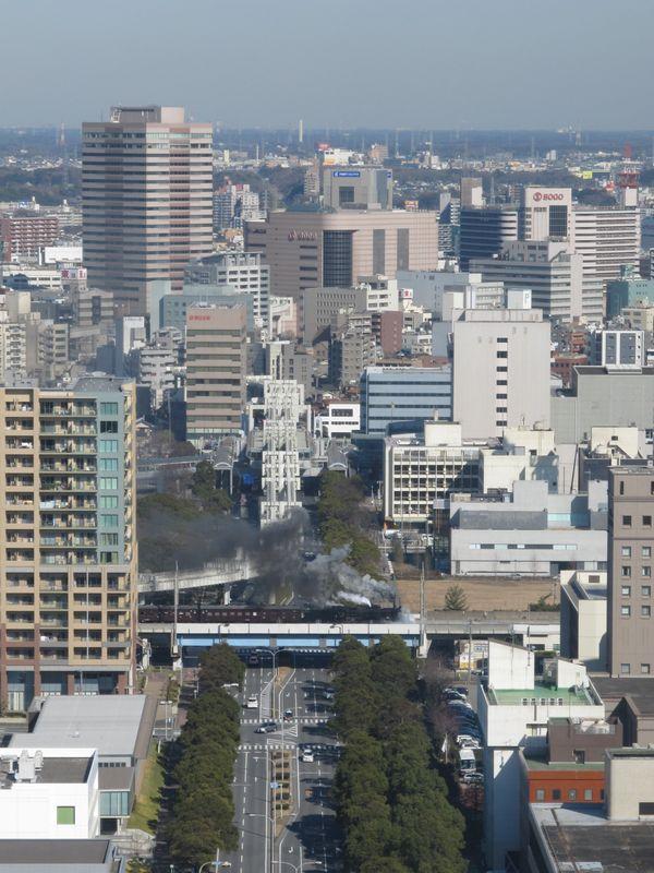 千葉市の市街地をバックに黒煙を上げながら走り出したSL内房100周年記念号。