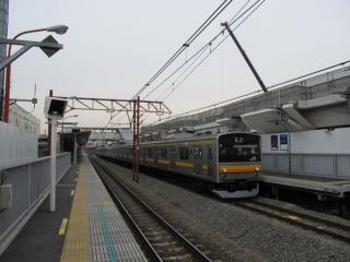 稲城長沼駅2番線に停車中の立川行き205系電車。背後では高架橋の建設が進む。