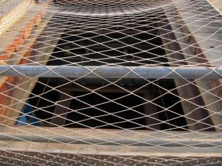 覆工板に開いている穴から中を覗く。かなり深いところまで掘削が進んでいる。