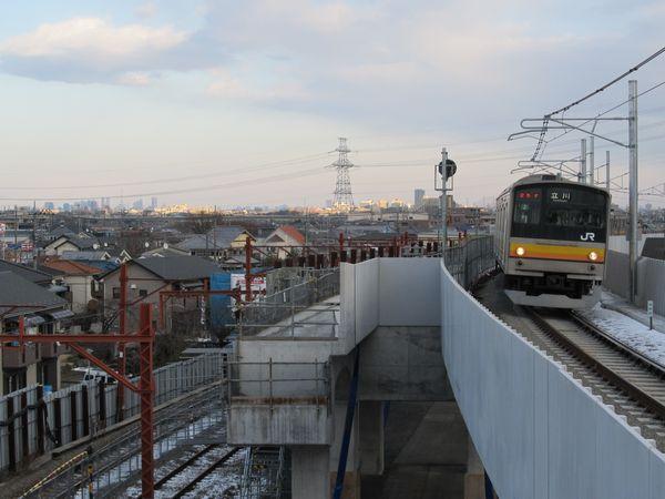 南多摩駅に進入する南武線205系。遠方には新宿副都心・東京スカイツリー。