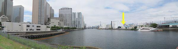 品川埠頭橋から見た京浜運河。トンネルは中央やや右の倉庫(黄色の↓)から画面左端の白い建物の下を通過する。