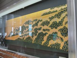 改札口前にある室瀬和美作の漆絵「木精」がある。